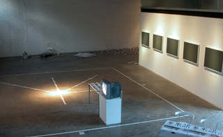 The Installation with marks in the space, video mornitor, photos on the table and the five framed aluminium boards.